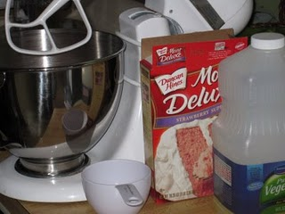 A box of strawberry cake mix beside a mixing bowl fitted with the whisk attachment
