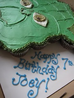 """A Yoda cake in a box with """"Happy 7th Birthday Joey"""" written in icing"""