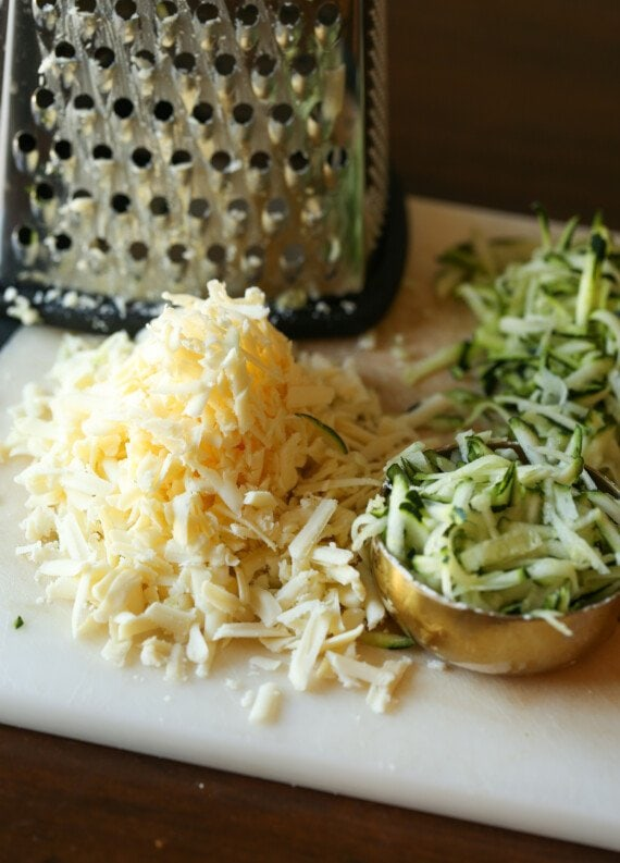 Grated zucchini and cheddar cheese on a cutting board