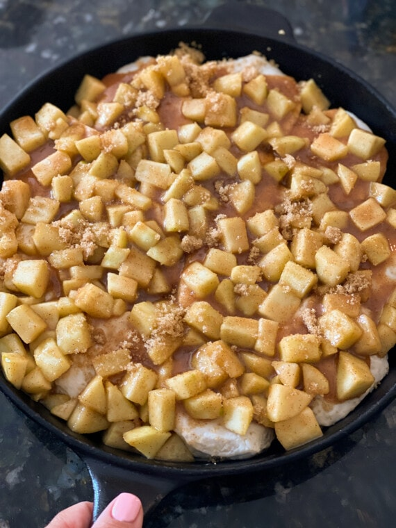 Biscuits in a cast iron skillet topped with apple pie filling and brown sugar
