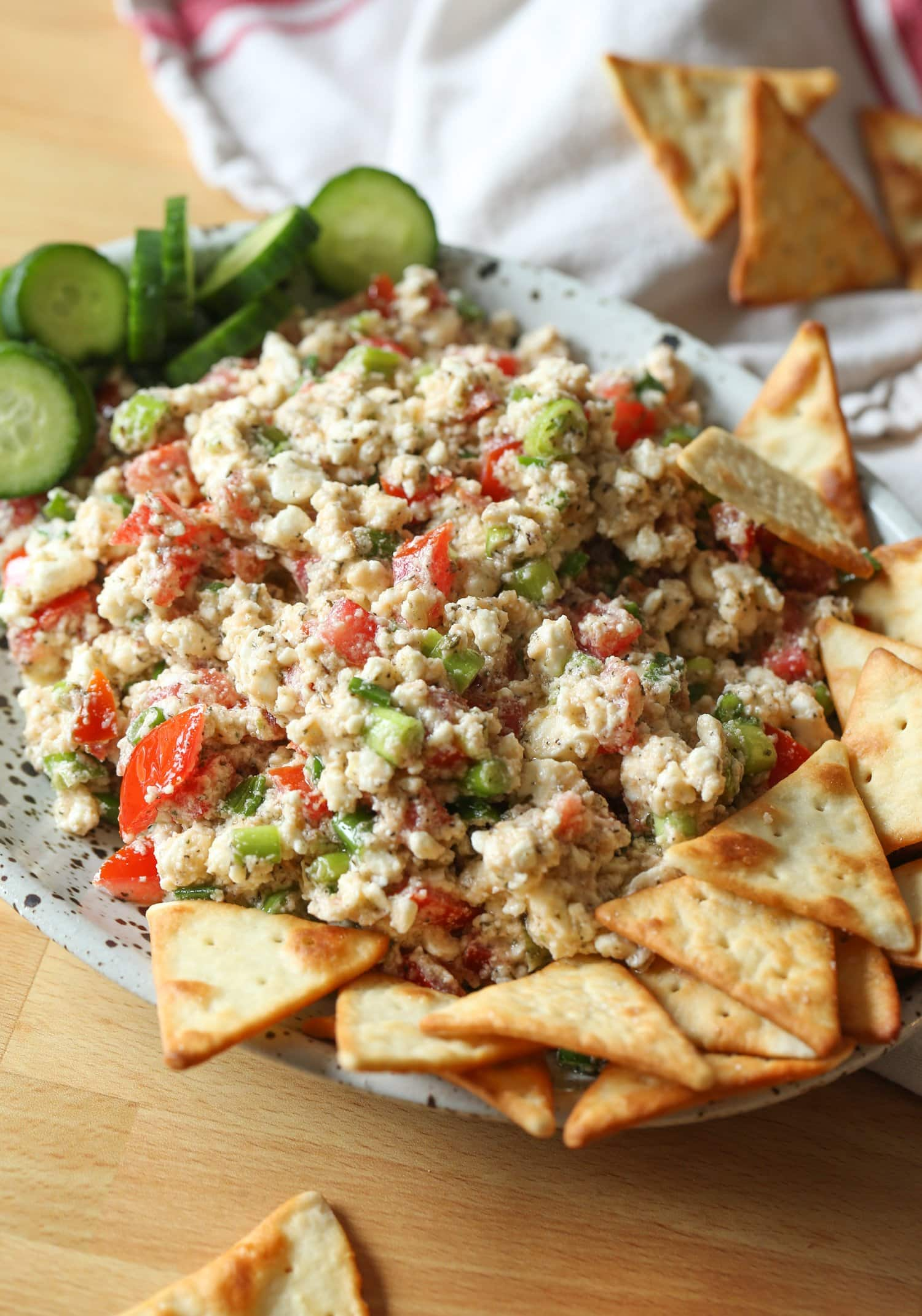 Dip on a platter with pita chips and veggies