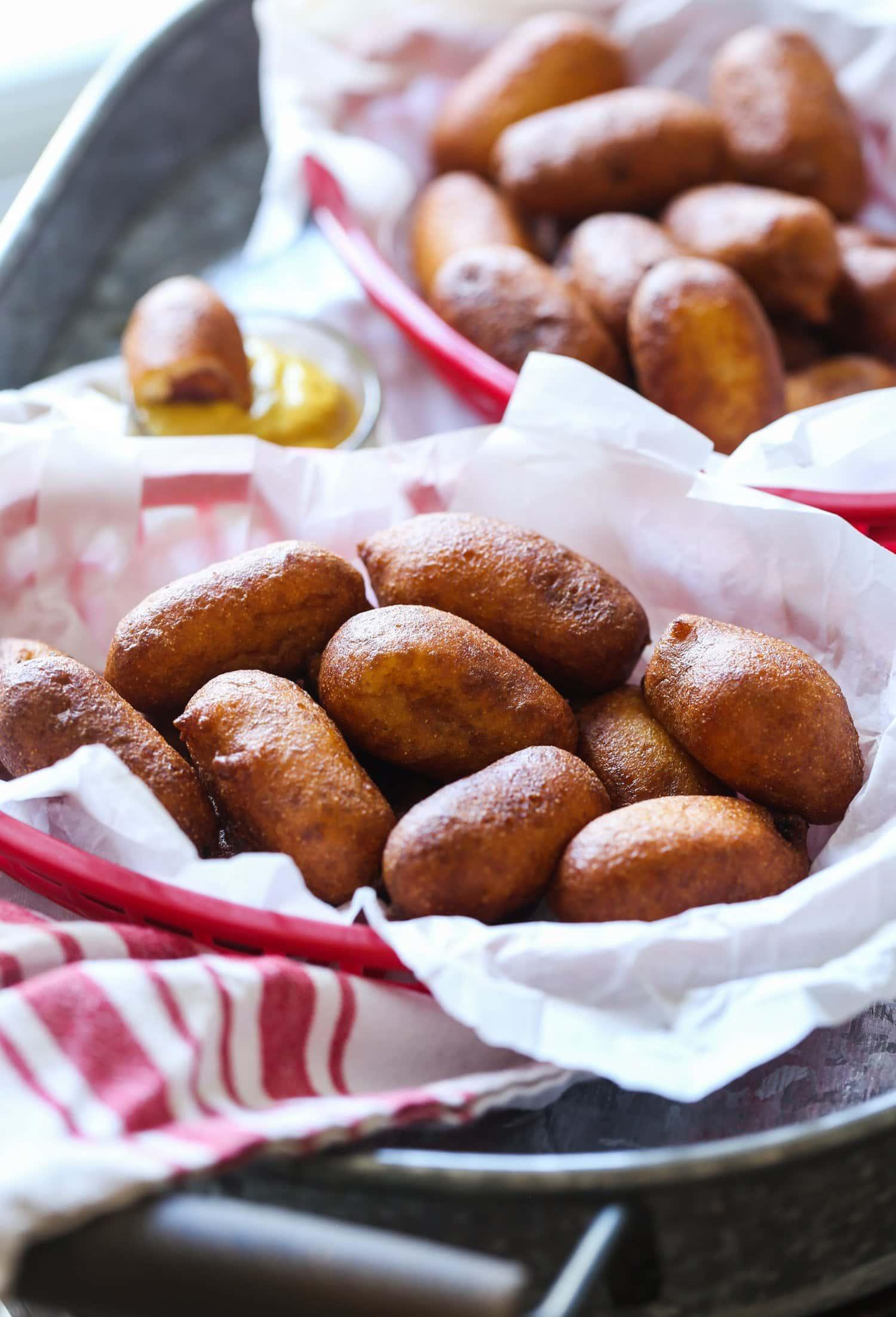 A basket of mini corn dogs with cornmeal breading.