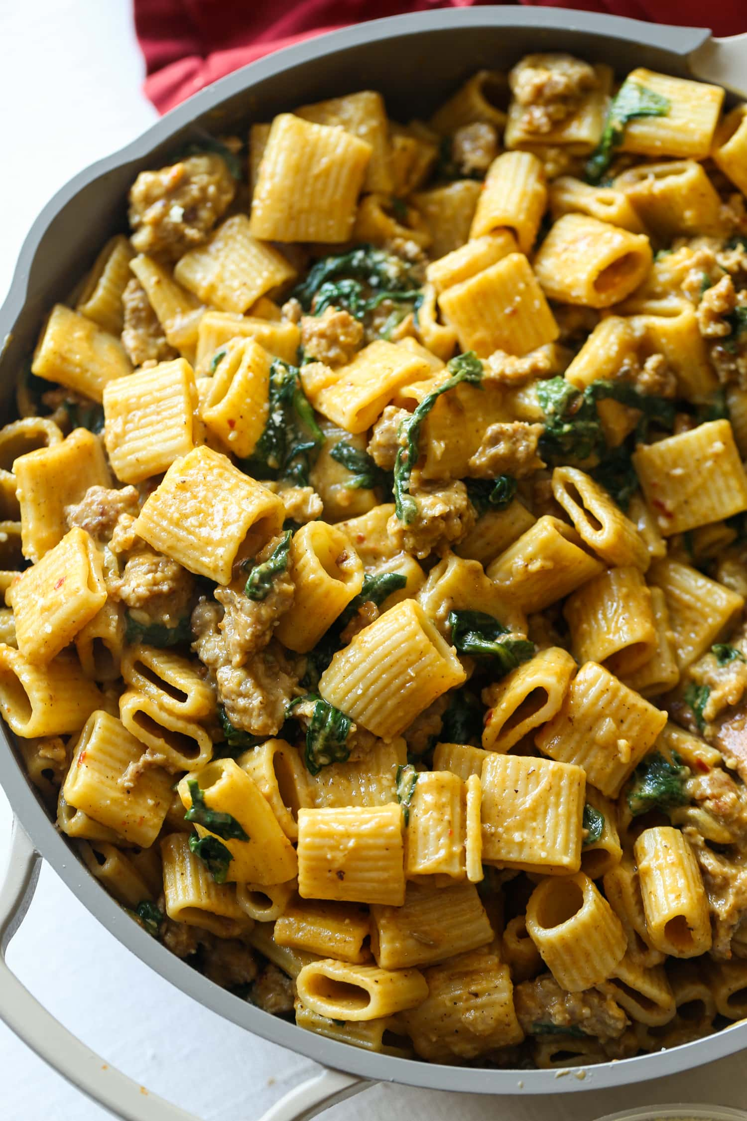 Noodles with sausage and spinach in a pumpkin cream sauce.