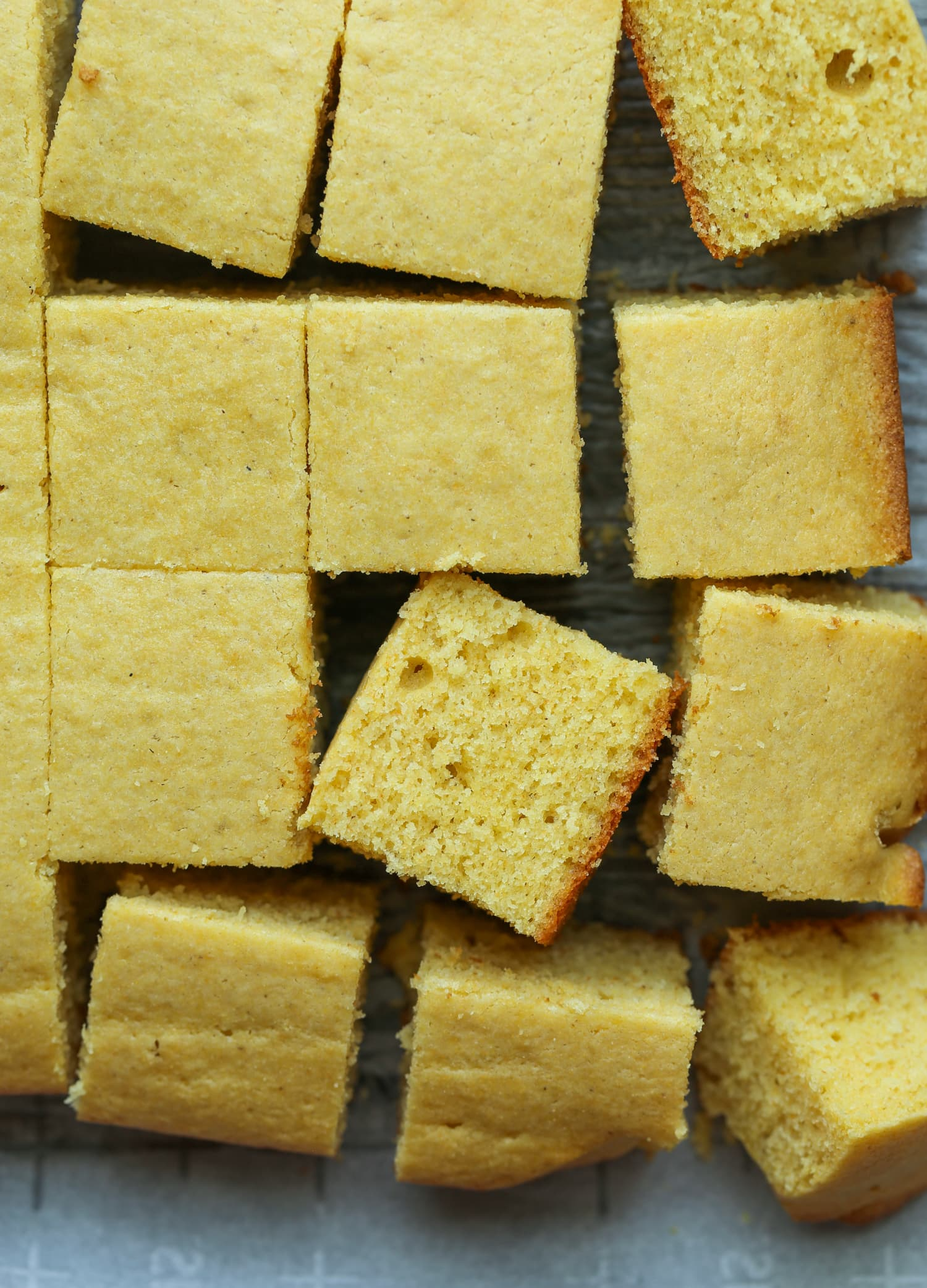 Cornbread cut into squares on a baking sheet.