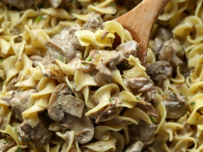 A portion of stroganoff with egg noodles being scooped out of a Crockpot with a wooden spoon.