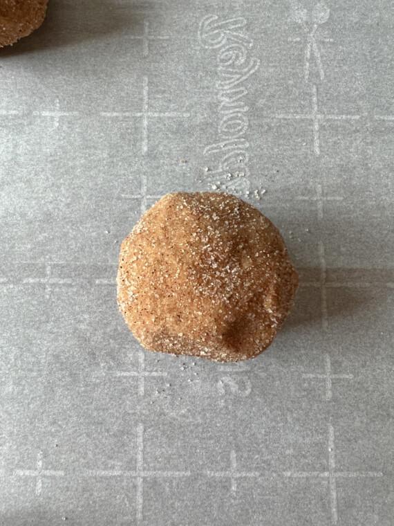 close up of pumpkin cookie dough ball coated in cinnamon sugar