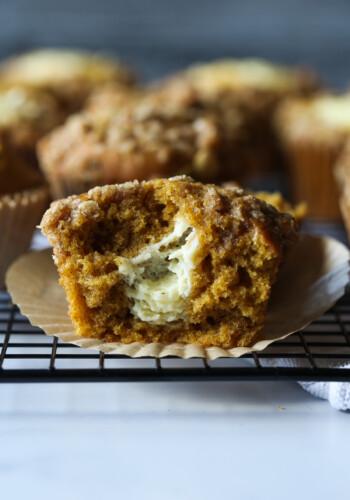 Pumpkin muffin broken in half with cream cheese filling