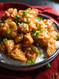Orange chicken with chopped green onions.